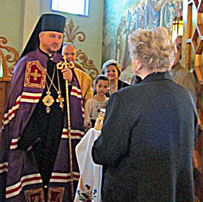 Image of Bishop Andrij being greeted by parish president.